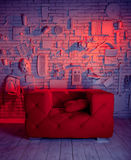 Pink sofa in artistic,creative interior. Photo Studio background for photography and a sofa.On the wall for decoration attached to various objects: electric Royalty Free Stock Image