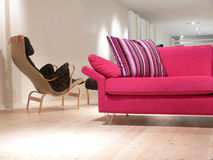 Pink Sofa and Chair. A pink sofa with pillows and an armchair on a pine wood floor Stock Image