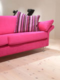 Pink Sofa and Pillow. A pink sofa with a striped pillow on a pine wood floor Stock Photos