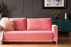 Pink sofa with pillows in grey living room interior with poster stock image