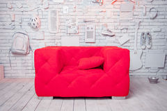 Pink sofa in white, creative interior. Photo Studio background for photography and a sofa.On the wall for decoration attached to various objects: electric Royalty Free Stock Photos