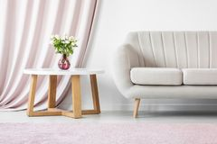 Pink sophisticated interior with flowers. Sofa next to a wooden table with white flowers in pink vase against pastel curtain in sophisticated interior Stock Images