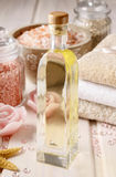 Pink spa set: bottle of rose essential oil, towels and sea salts Royalty Free Stock Image
