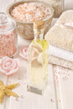 Pink spa set: bottle of rose essential oil, towels and sea salts Royalty Free Stock Images