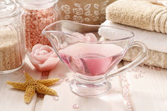 Pink spa set: liquid soap, scented candles, towels and rose sea Stock Photos
