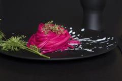 Pink spaghetti, black place setting Royalty Free Stock Photo