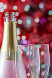 Pink sparkling wine bottle with flutes Stock Photography