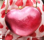 Pink sparkly heart purse with a gold chain strap hanging in front of a red heart print scarf stock images