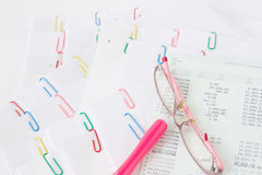 Pink spectacles and pen with book bank Stock Photography