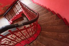 Pink spiral staircase in the old house with pink walls. Stairs with handrails in historical building stock photography