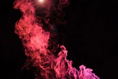 Pink spiritual smoky swirl with light. On black background royalty free stock photography