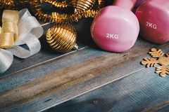 Pink sport dumbbells with Chrismas decoration items and gift bow. On wooden background, Merry Christmas and Happy new year wish sport gifts concept Stock Photos