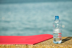 Pink sport mat and water bottle outdoor on sea shore Stock Image