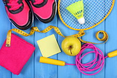 Pink sport shoes, fresh apple and accessories for sport on blue boards, copy space for text on sheet of paper Stock Photos