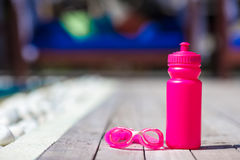 Pink sporty water bottle near swimming pool Stock Photo