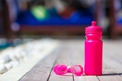 Pink sporty water bottle near swimming pool Stock Photo