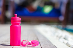 Pink sporty water bottle near swimming pool Royalty Free Stock Images