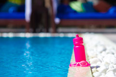 Pink sporty water bottle near swimming pool Stock Photos