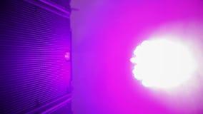 Pink spotlight turning around and lighting concert hall, electronics, light show