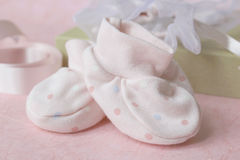 Pink spotted baby bootees. Pair of pink spotted baby bootees in front of gift box lid, gift bag and pink satin ribbon Stock Photography