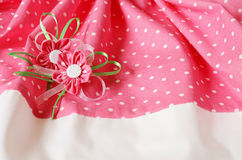 Spotted fabric background with artificial flowers Stock Photography
