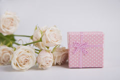 Pink spotted gift box and creamy roses on white background Royalty Free Stock Photo