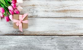Pink springtime tulips and gift box on white rustic wooden board Royalty Free Stock Images