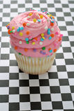 Pink sprinkle cupcake on checkered background Royalty Free Stock Images