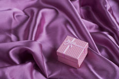 Pink squared gift box on purple satin fabric folds Stock Photography