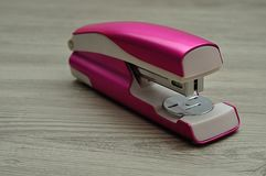 A pink stapler. On a table stock photo