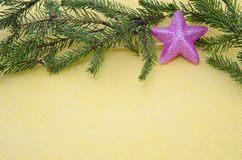 Pink star ornament with fir branches on yellow royalty free stock image
