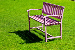 The pink steel bench  On green grass.  Royalty Free Stock Photography