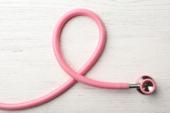 Pink stethoscope folded like awareness ribbon on wooden background, top view. Breast cancer concept stock photos