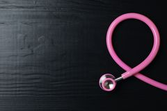 Pink stethoscope folded like awareness ribbon on wooden background, top view with space for text. Breast cancer concept stock image