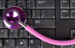 Pink stethoscope on keyboard Stock Photography