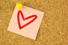 Pink sticker with draw heart on the corkboard Royalty Free Stock Images