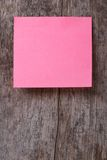 Pink sticker on an old wooden table. close up Royalty Free Stock Photos
