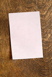 Pink Sticky Note. Blank pink sticky note on wood desk, vertical Royalty Free Stock Images