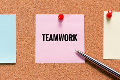 Pink sticky note on cork board with teamwork word and push red p Stock Photos
