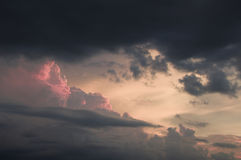 Pink Storm. Clouds in the distance at sunset with dark clouds overhead stock photography