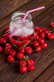 Pink straw in jar among heap of cherries Royalty Free Stock Photo