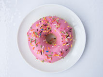 Pink Strawberry Donut. Close up top view of Pink Strawberry Donut decorated with colorful sugar topping on a white plate isolated on white background Royalty Free Stock Photography