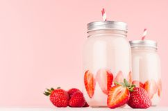 Pink strawberry smoothies with piece juicy fruits in retro jars with red striped straws on light soft pastel pink wall. Pink strawberry smoothies with piece stock image