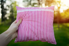 Pink striped pillow holding in hand closeup Royalty Free Stock Photography