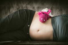 Pink stuffed dragon toy on belly Stock Image