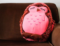 Pink stuffed owl on brown couch Stock Photography