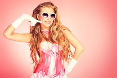 Pink style. Portrait of a charming blonde woman posing in studio over pink background Stock Photos