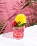 Pink Summer cold alcoholic cocktail on a white bar table. Green palm tree leaves on the background. Copy space for your text. Hard light stock images
