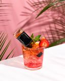 Pink Summer cold alcoholic cocktail on a white bar table. Green palm tree leaves on the background. Small bottle of whisky, mint and strawberry. Copy space for royalty free stock photography