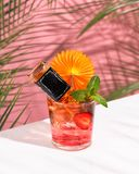 Pink Summer cold alcoholic cocktail on a white bar table. Green palm tree leaves on the background. Small bottle of whisky, mint and strawberry. Copy space for royalty free stock photos